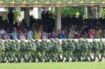 Military with full packs and women spectators in traditional dress