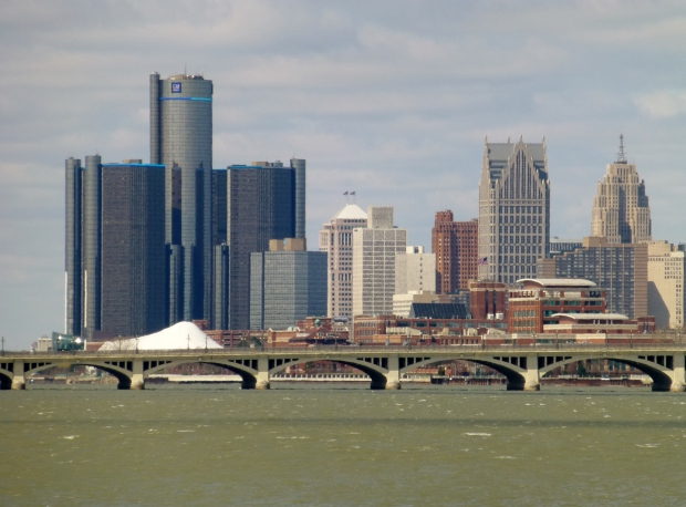 Renaissance Center (GM HQ) on left, Fisher Building on right, Detroit River, and Belle Isle Bridge (foreground)