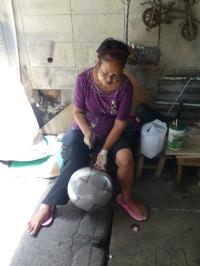 Craftswoman hammering bowl